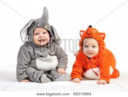 Two baby boys dressed in animal costumes on white