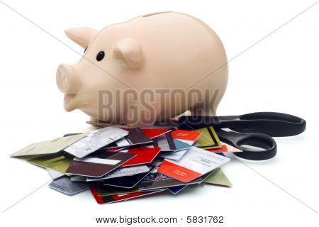 Piggy Bank, Scissors, And Cut-up Credit Cards Against White Background