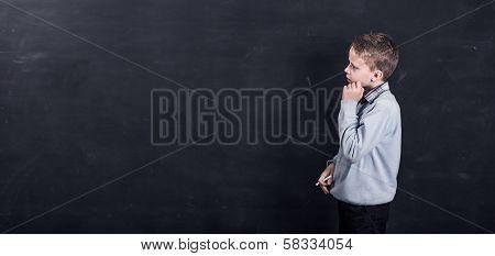 Child writing on black chalkboard
