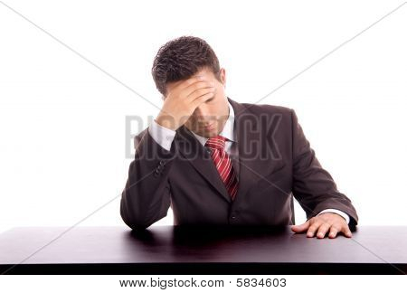 Young Business Man On A Desk Gestures With A Headache