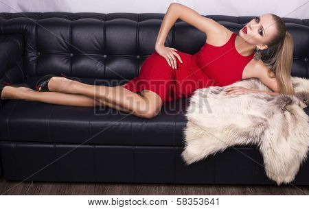 sexy girl in red dress lying on the black leather divan