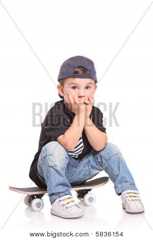 Little child sitting on a skateboard