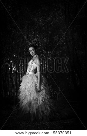 Monochrome image of beautiful fantasy woman wearing an evening dress in a forest
