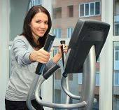 Young Woman Doing Exercise On A Elliptical Trainer