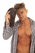 foto of chest  - A man with his shirt open showing off his chest putting on his western hat - JPG