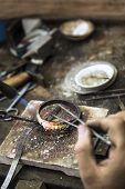 image of torches  - Vertical close up shot of Jeweler crafting golden rings with flame torch - JPG