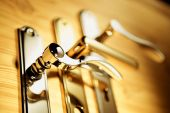image of front door  - A series of golden handles on a wooden board - JPG