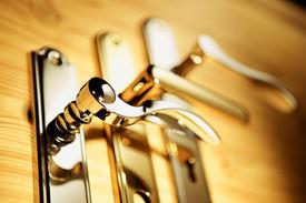 image of door-handle  - A series of golden handles on a wooden board - JPG
