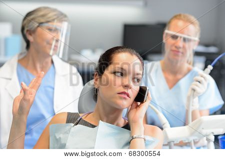 Impolite businesswoman on phone in dental office letting dentist wait