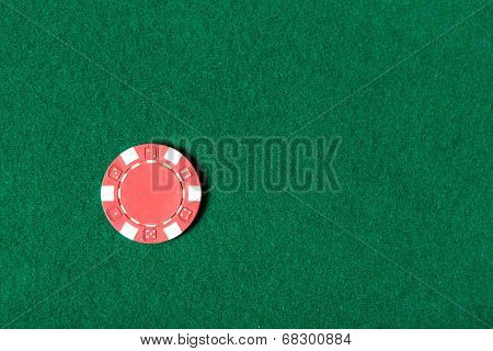 Top view of red poker chip on the green table. Risky entertainment of gambling