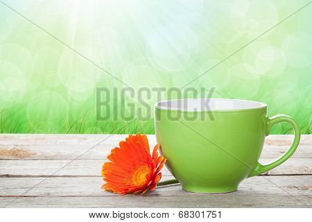 Cup of coffee and gerbera on wooden table with sunny bokeh