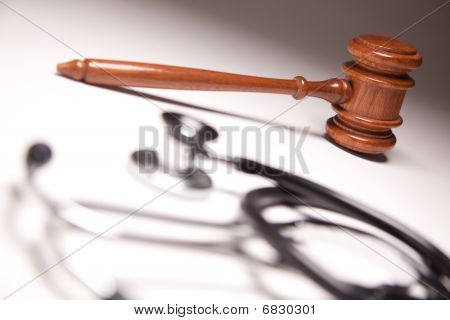 Gavel And Stethoscope On Gradated Background