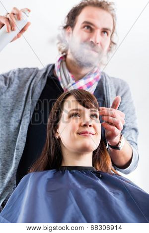 Male coiffeur giving women hairstyling with hairspray in shop