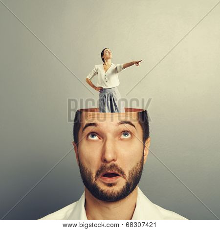amazed young businessman with open head. young emotional businesswoman standing into the head and showing the direction. photo over grey background