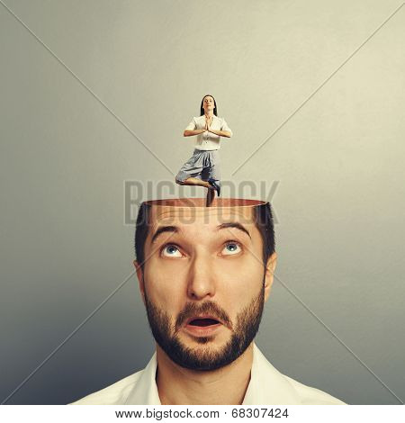 amazed young man with open head. calm yoga businesswoman standing into the head. photo over grey background