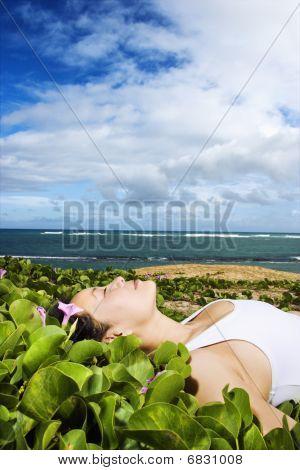 Woman Lying In Plants Near Beach