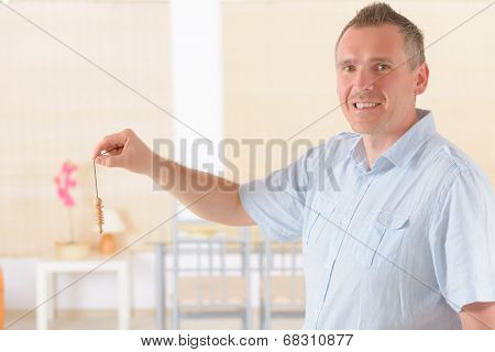 Man dowser using wooden pendulum, tool for dowsing.
