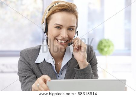 Portrait of beautiful young female dispatcher using headphones, smiling, looking at camera.