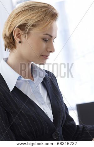 Side view of young businesswoman thinking.