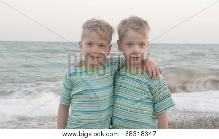 identical twin children on the beach