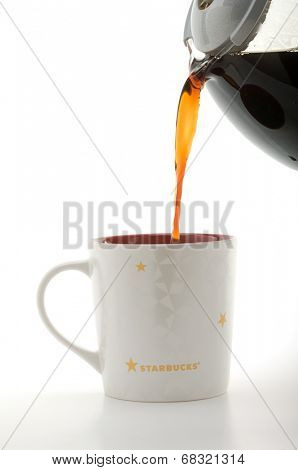 Ankara, Turkey - May 31, 2012:  Pouring filter coffee in newly designed Starbucks coffee mug isolated on white background