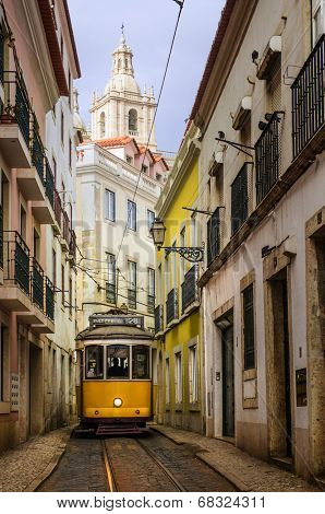 Narrow street in old Lisbon downtown with typical yellow tram