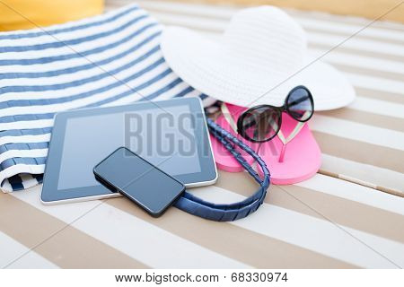 beach, summer, vacation, accessories and technology concept - close up of tablet pc computer, smartphone and summer accessories on beach