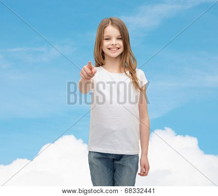 gestures and happy people concept - happy little girl in blank white t-shirt pointing at you