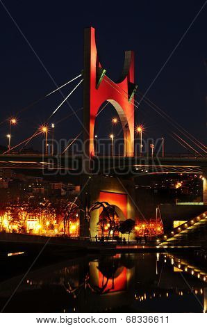 BILBAO, SPAIN - NOVEMBER 14: Principes de Espana Bridge in the evening on November 14, 2012 in Bilbao, Spain. The bridge is topped with a red porch designed by french architect Daniel Buren