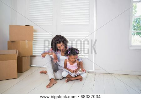 Mother and daughter sitting on the floor reading storybook in their new home