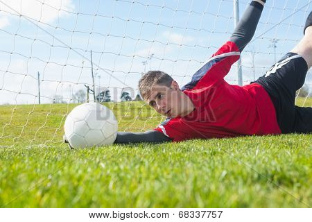 Goalkeeper in red making a save during a match