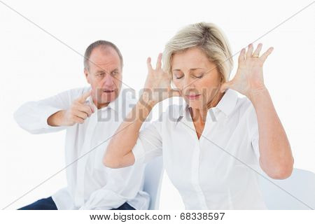 Older couple sitting in chairs arguing on white background