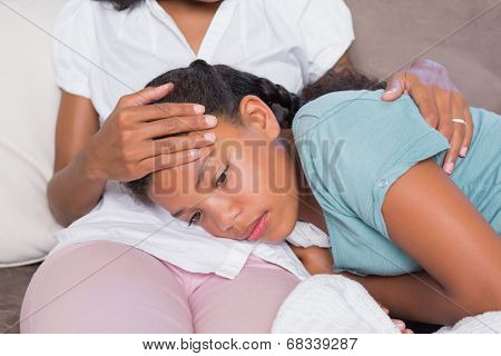 Sick daughter lying on mothers lap at home in living room