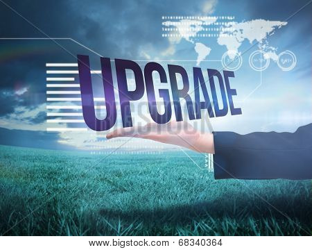 Businesswomans hand presenting the word upgrade against blue sky over green field