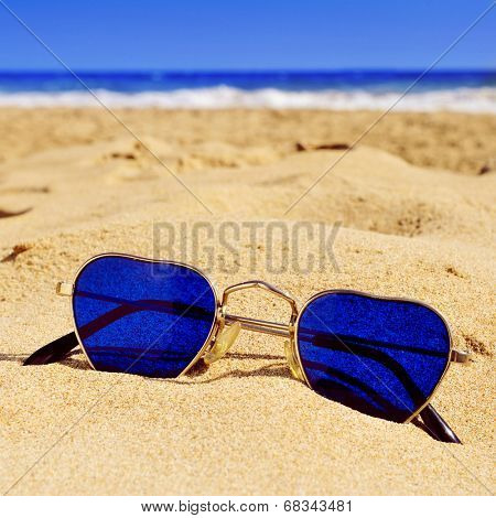 closeup of a pair of heart-shaped sunglasses in the sand of a beach