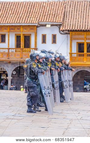 CUZCO, PERU, MAY 1, 2014 - Policemen in tactical vests and special equipement control the 1 May manifestation in Plaza de Armas