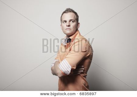 Man posing on a white wall