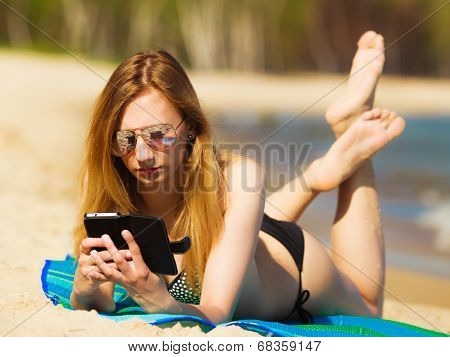 Summer Vacation Girl With Phone Tanning On Beach