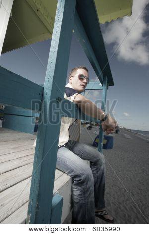 Man sitting on a lifeguard hut