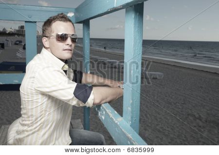 Handsome man on a lifeguard tower