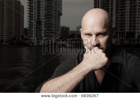 Bald headed male posing by the bay
