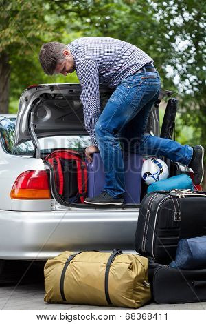 Man Using His Strength To Packing Luggage Into Car