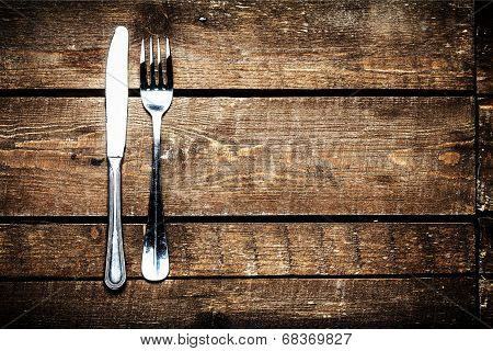 Silver Knife and fork over wooden table