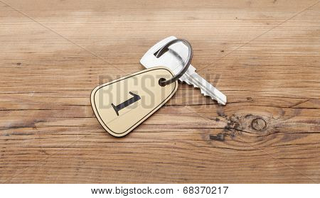 Closeup of an key of room number 1 with key on a wooden desk