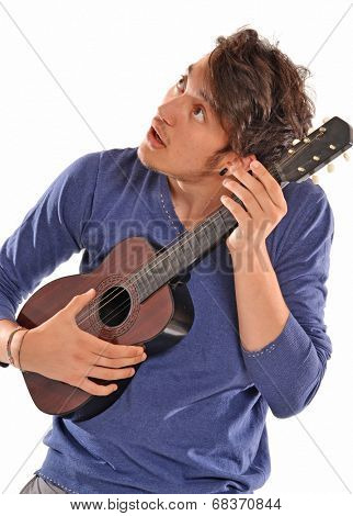 Young man holding and playing a guitar.Tuning guitar.