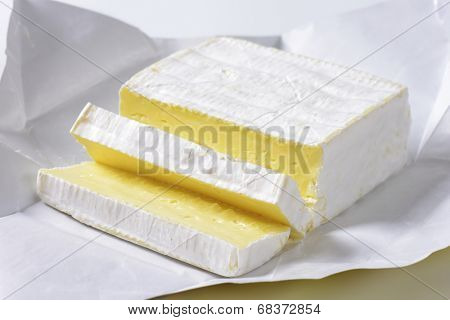 detail of sliced cow's cheese in a paper wrapper