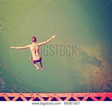 a boy jumping of an old train trestle bridge into a river done