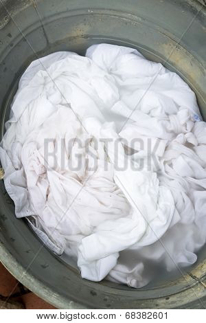 Soiled laundry in an old bucket