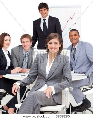 Assertive Female Executive Sitting In Front Of Her Team
