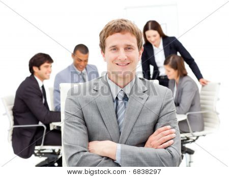 Assertive Male Executive With Folded Arms Sitting In Front Of His Team